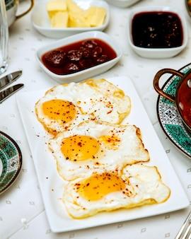 Un plato de tres huevos con pimiento rojo.