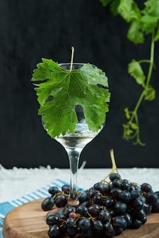 Un plato de uvas negras y una copa de vino con hojas sobre fondo oscuro. foto de alta calidad