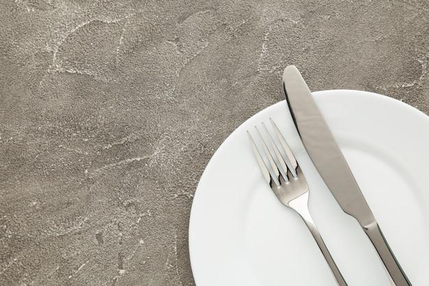 Plato vacío blanco con tenedor y cuchillo sobre una mesa gris
