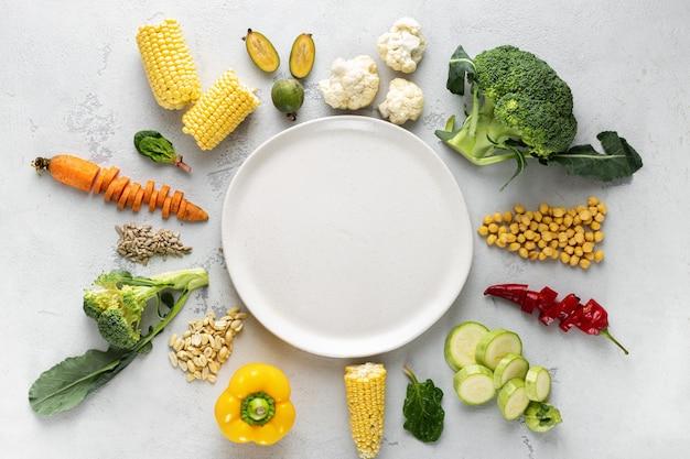 Plato vacío con comida vegetariana. ingredientes frescos para cocinar vista superior de plato vegano