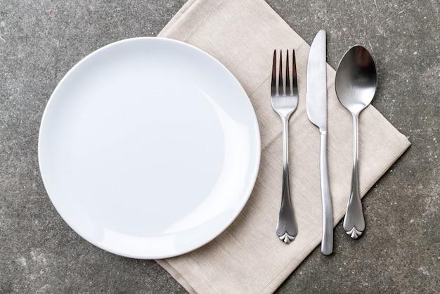 Plato vacio cuchara tenedor y cuchillo