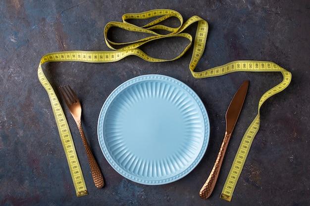Plato vacío, cuchillo, tenedor y cinta métrica