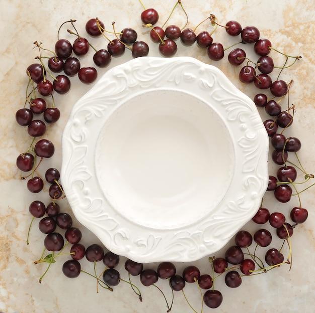 Plato vacío y esparcido alrededor de cerezas