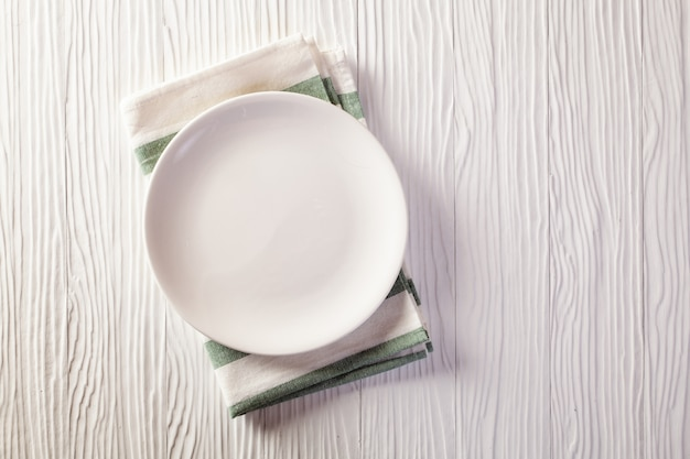 Plato vacío en mantel a cuadros en la mesa de madera blanca