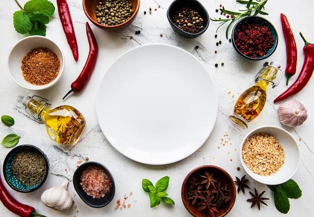 Plato vacío y marco de especias, hierbas y verduras