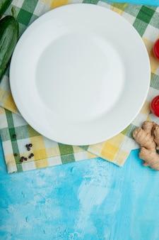Plato vacío con pepino, jengibre, pimienta y condimentar sobre un paño en la mesa azul