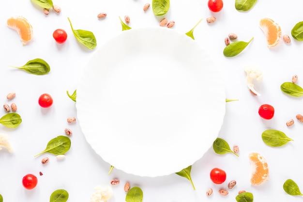 Plato vacío rodeado de frijol pinto; verduras y rodajas de naranja dispuestas sobre fondo blanco