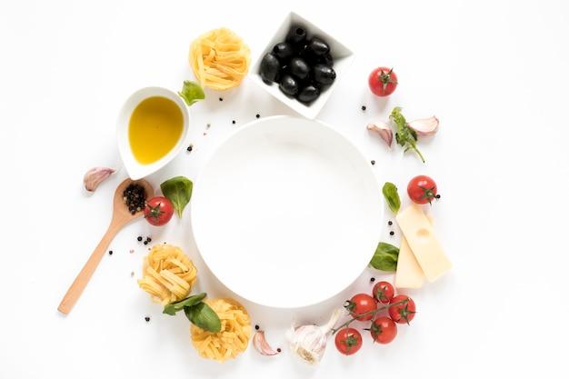 Plato vacío rodeado de ingrediente de pasta italiana y cuchara de madera aislada sobre fondo blanco