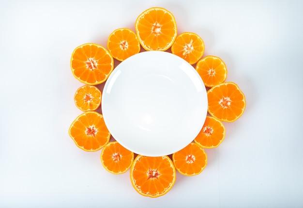 Plato vacío rodeado de mandarinas en rodajas con espacio de copia en superficie blanca