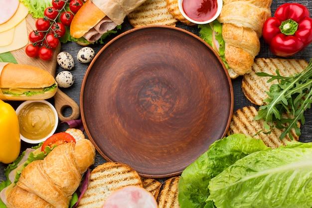 Plato vacío rodeado de sandwiches