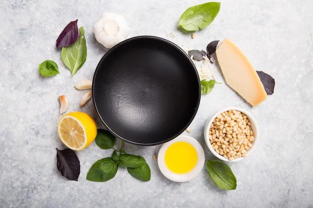 Plato vacío para salsa pesto de albahaca italiana con ingredientes culinarios para cocinar