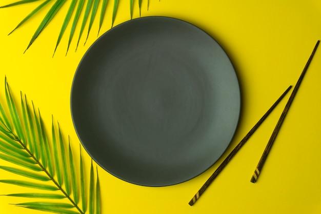 Plato vacío sobre un fondo amarillo. plato vacío para comida y cocina asiática y china con palillos chinos