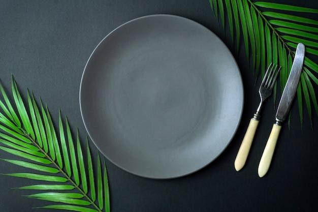Plato vacío sobre un fondo oscuro. placa de cerámica gris vacía con un cuchillo y tenedor para comida y cena en un hermoso fondo oscuro.
