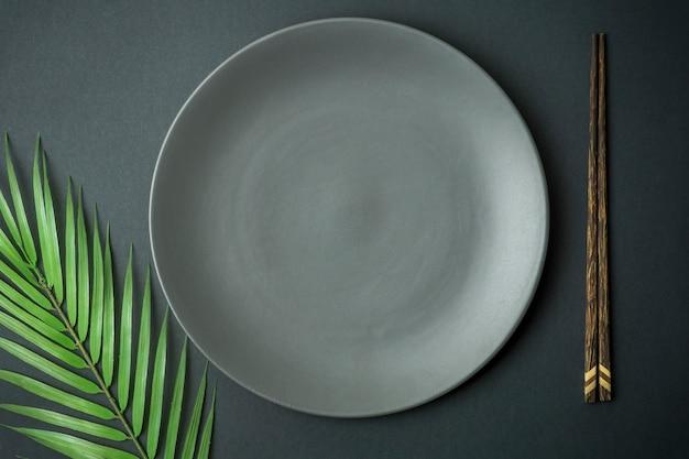 Plato vacío sobre fondo oscuro. plato vacío para comida y cocina asiática y china con palillos chinos