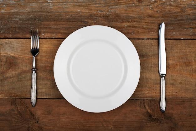 Plato vacío con tenedor y cuchillo en la mesa de madera vintage