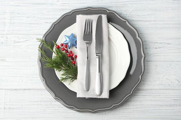 Plato vacío, tenedor y cuchillo sobre fondo de madera