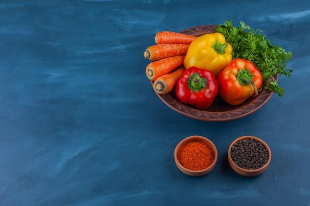 Plato de varias verduras frescas maduras en azul.