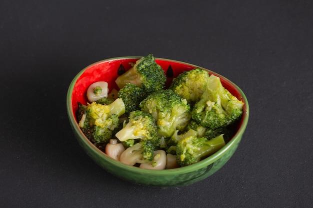 Plato vegetariano de brócoli hervido con aceite de oliva, trozos de col verde en un recipiente sobre la mesa