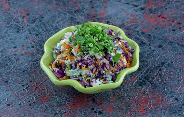 Un plato verde de ensalada de verduras con hierbas.