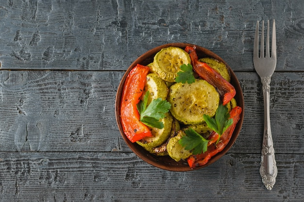 Un plato de verduras al horno y un tenedor sobre una mesa de madera negra