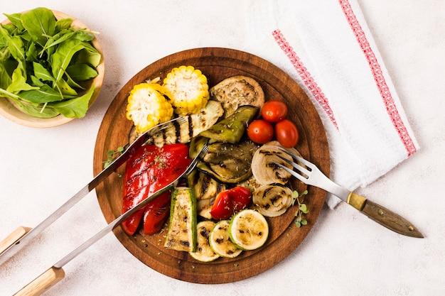 Plato con verduras asadas y cubiertos en mesa