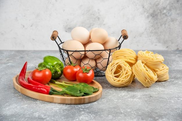 Plato de verduras frescas y nidos de fideos en la superficie de mármol.