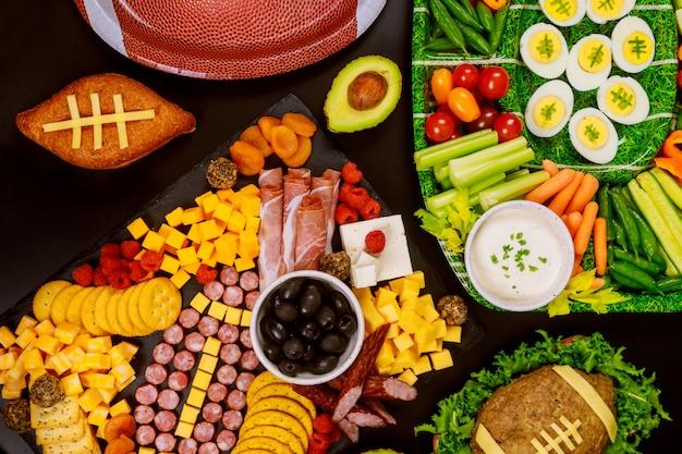 Plato de verduras recién cortadas con tablero de charcutería para la fiesta del juego de fútbol americano