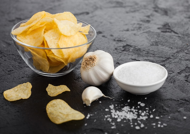 Plato de vidrio con papas fritas con sabor a cebolla con ajo y sal sobre piedra negra