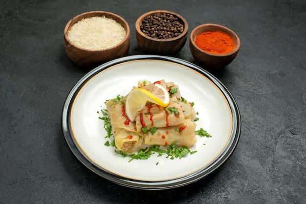 Plato de vista lateral de primer plano con especias apetitoso repollo relleno con salsa de limón y hierbas y tazones de especias coloridas arroz y pimienta negra sobre fondo oscuro