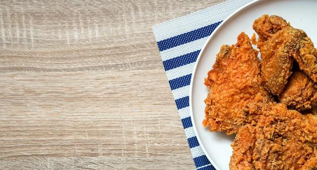 Plato de vista op de pollo frito en el fondo de mesa de madera de restaurante