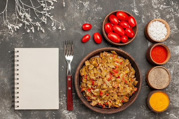 Plato de vista superior y especias plato de horquilla de cuaderno blanco de frijoles y especias de colores sobre la mesa negra