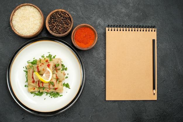 Plato de vista superior y especias repollo relleno con salsa de limón y hierbas y tazones de especias de colores, arroz y pimienta negra en la mesa junto al cuaderno de crema y lápiz