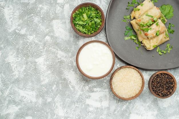 Plato de vista superior con hierbas plato de repollo relleno junto a cuencos de hierbas, arroz con crema agria y pimienta negra en el lado derecho de la mesa