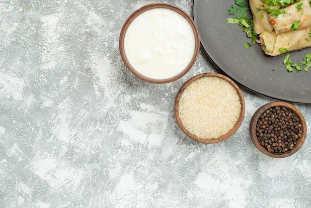 Plato de vista superior con hierbas plato de repollo relleno junto a tazones de arroz con pimientos negros y crema agria en el lado derecho de la mesa
