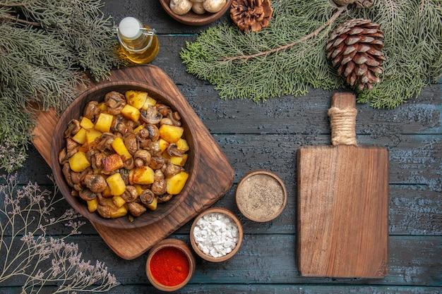 Plato de vista superior del plato de comida de champiñones y patatas junto a diferentes especias y tabla de cortar debajo de la botella de aceite tazón de fuente de champiñones blancos y ramas de abeto con conos