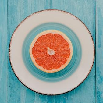 Plato de vista superior con pomelo en la mesa