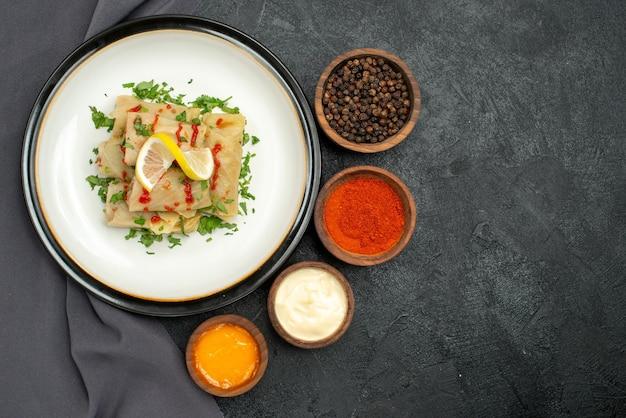 Plato de vista superior de primer plano y mantel plato blanco de repollo relleno con hierbas limón y salsa