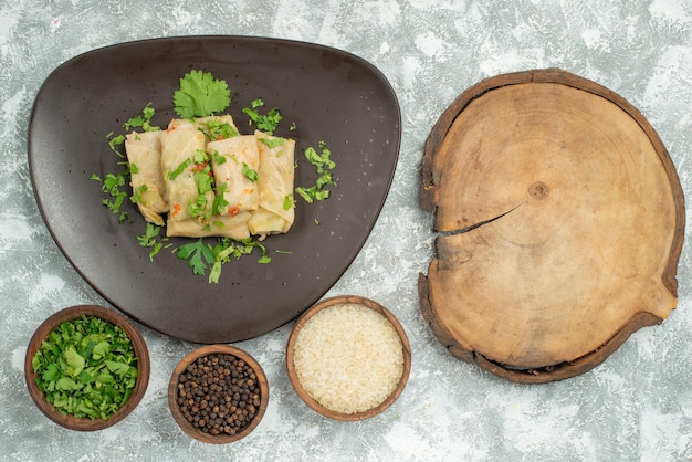 Plato de vista superior de primer plano del plato de comida de repollo relleno y platos de arroz papper negro y hierbas en el lado izquierdo de la mesa junto a la tabla de cortar de madera