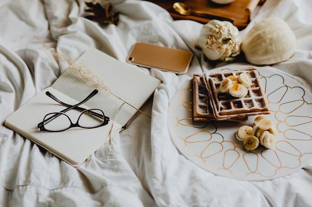 Plato de waffle de desayuno con cobertura de plátano sobre una cama blanca junto a un diario y un teléfono