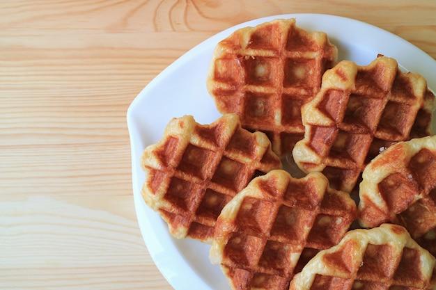 Plato de waffles belgas servido en mesa de madera