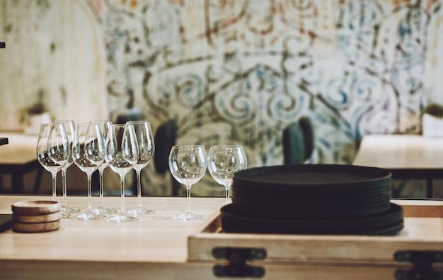 Platos de arcilla marrón natural y copas de cristal en un café.