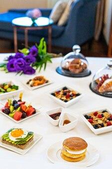 Platos de bandeja con desayuno variado en una cama en una habitación de hotel