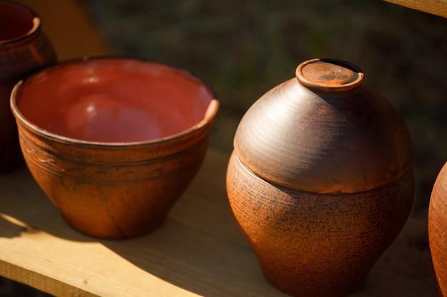 Los platos de barro marrón están en un estante de madera. bajo el brillante sol de verano