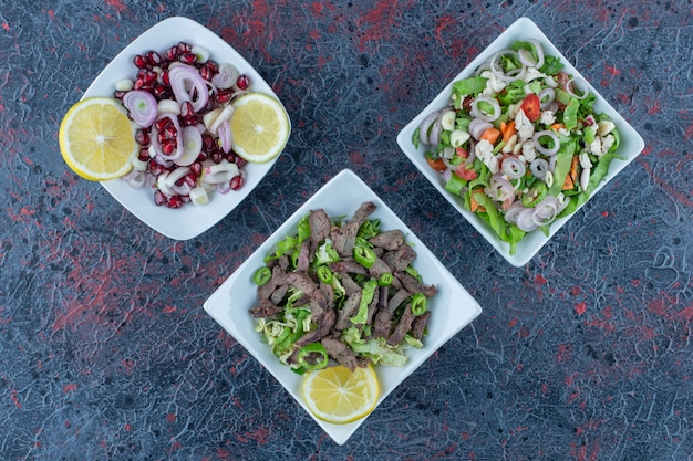Platos blancos de ensaladas de carne y verduras.