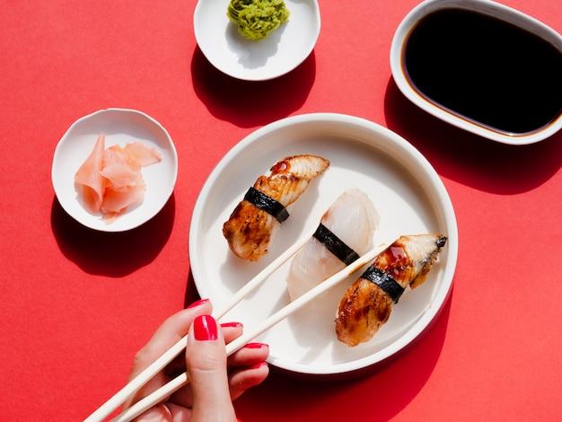 Platos blancos con sushi y wasabi sobre un fondo rojo.