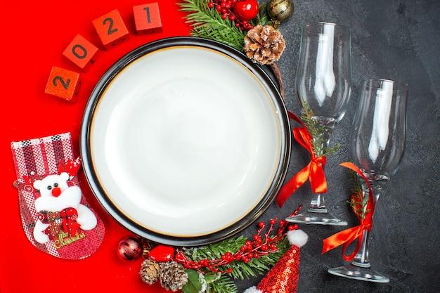 Platos de cena, accesorios de decoración, ramas de abeto, números de calcetines navideños en una servilleta roja y copas de vidrio en la mesa oscura