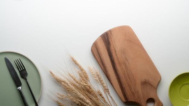 Platos de cerámica, bandeja de madera, cubiertos, espacio de copia y trigo dorado decorados en la mesa de comedor