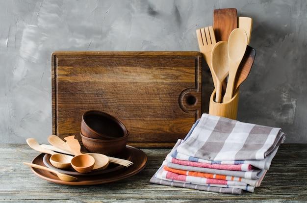 Platos de cerámica, cubiertos de madera o bambú, tabla de cortar vintage y toallas en el interior de la cocina.