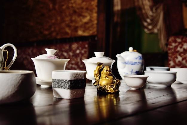 Platos para la ceremonia del té y la figura hotei en la mesa del té.