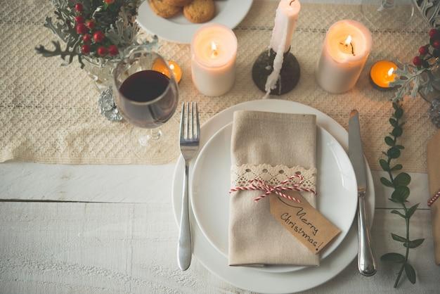 Platos, cubiertos, servilletas y copa de vino preparadas para la cena de navidad en la mesa con velas.